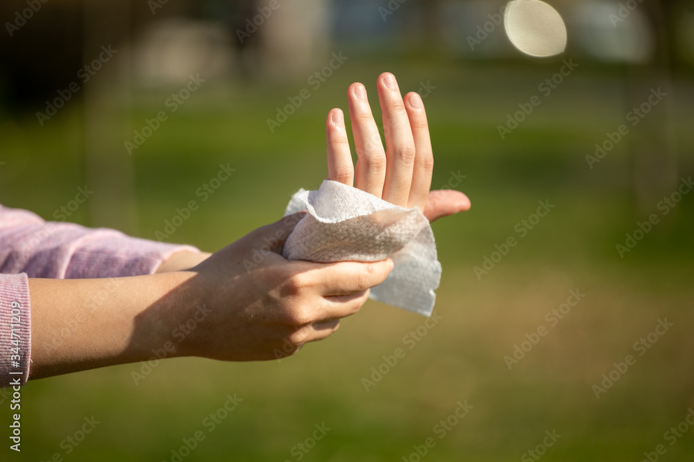 Fototapeta Cleaning hands and fingers with wet wipes against disease infection like flu or influenza