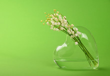 Flowers In Heart Shape Glass Against Green Background