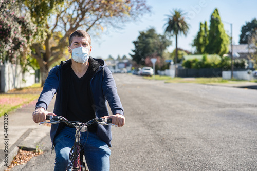 young caucasian man wearing face mask and riding his bicycle on the street Tableau sur Toile