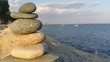 Stacked Stones By Sea Against Sky