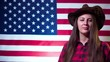 A woman with long hair in a cowboy hat against the background of the American flag shows a cowboy greeting touching her hat.