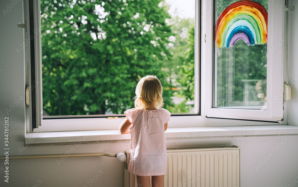 Fototapeta Little girl looks out  open window at home at spring time.