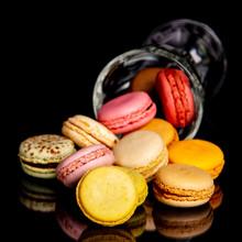 Macarons Multicolores Sortant D'un Verre Sur Fond Noir