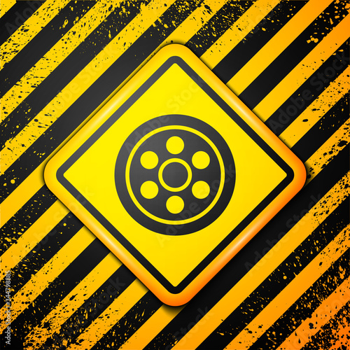 Photo Black Alloy wheel for a car icon isolated on yellow background