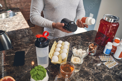 Sportsman with sports nutrition at the table Fotobehang
