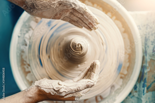 Fototapeta Close-up of female hands sculpting clay on a Potter's wheel. Concept of hobby and cretivity at home and in the Studio workshop obraz