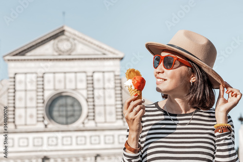 Fototapeta Hipster girl eats popular Italian Gelato ice cream in the background of a tourist attraction obraz