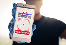 Man Holding A Smartphone With Non-Immune Digital Passport For Covid-19. Suitable For Immunity Passport App On The Phone To Monitorize The Population Movements At The End Of The Lockdown