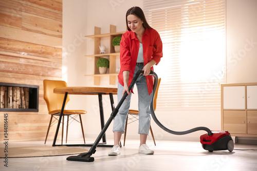 Fototapeta Young woman using vacuum cleaner at home