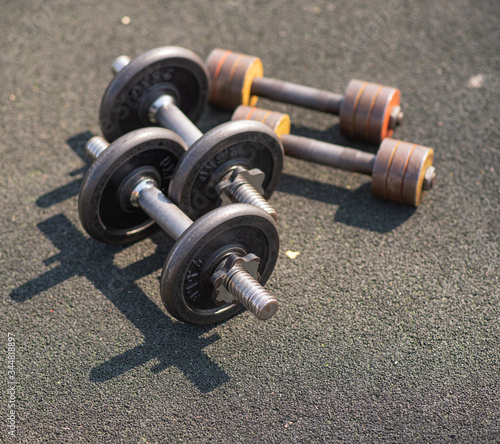 Two pairs of old dumbbells lie on the floor on a sports field on the street Canvas Print