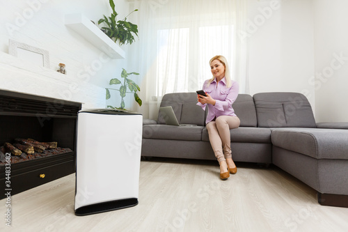 Fototapeta Young woman relaxing on the couch while air humidifier or purifier working on the foreground. Controlling it with a smartphone remotely obraz