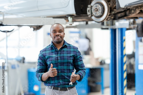Auto mechanic repairing a car, standing over a raised car on a lift, showing cool, holding a wrench in his hand