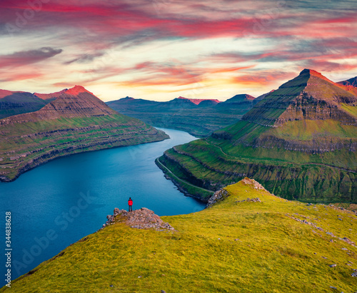 Photo Lonely hiker admiring spectacular sunset on Faroese fjords in the outskirts of Funningur village