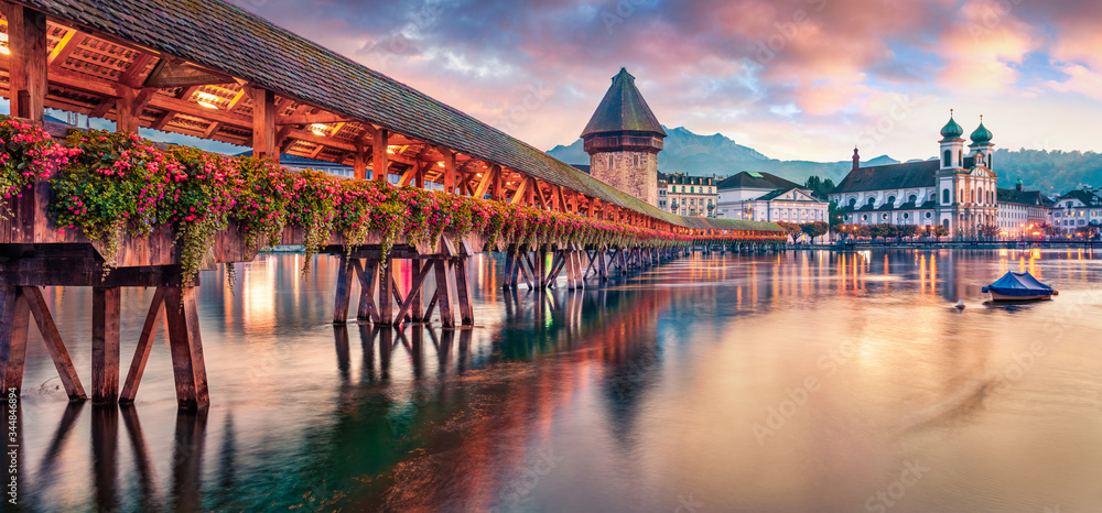 Fototapeta Famous old wooden Chapel Bridge (Kapellbrucke), landmark 1300s wooden bridge with grand stone water tower & a roof decorated with 17th-century art. Lucerne cityscape, Switzerland, Europe.