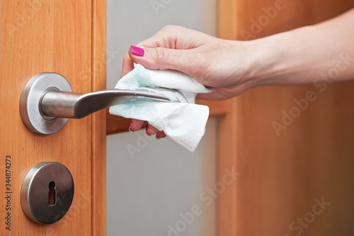 Hand cleaning metal door handle with paper tissue towel, closeup detail - corona Canvas Print