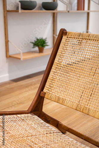 Photo Detail of backrest of modern wicker chair standing in a living room with gray wall and shelves with decorations and plants