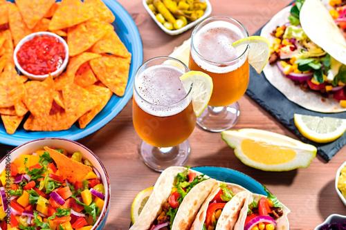 Table with tacos, mango salsa, nachos with sauce, guacamole, lemon beer for Cinco de Mayo celebration party Canvas Print