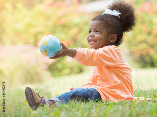 Cute little dark skinned toddler girl holding globe, world, earth ball toy with happiness in the park Canvas Print