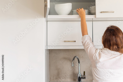 Photo Back view of woman putting or taking clean plate on the shelf in kitchen cupboard