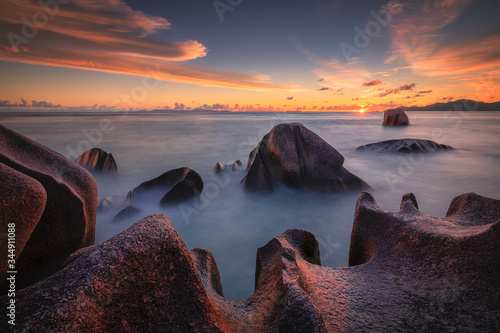 Beautiful colourful sunset on the beach with granite rocks in Seychelles. - 344911088