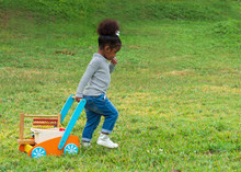 Cute Little Dark Skinned Toddler Girl Pulling Wooden Toy Wagon Full Of Toys And Books Across The Park