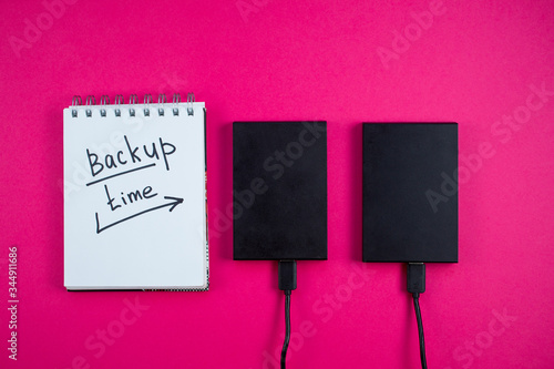 two hard drives and a Notepad with text backup time lie on a pink background Canvas Print