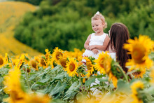 Happy Mother With The Daughter In The Field With Sunflowers. Mom And Baby Girl Having Fun Outdoors. Family Concept.
