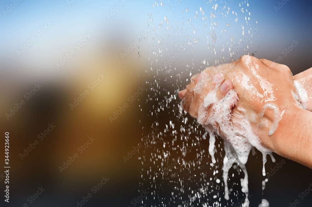 Fototapeta Man washing hands in clean water on blur background