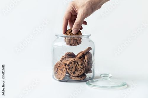 Obraz na płótnie A hand taking cookies from a glass jar on white background.