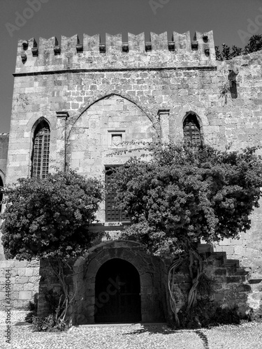 Canvas Print Rhodos, Greece, July 7th, 2019 - Black and White Photography of an Old building with Bougainvillaea flowers