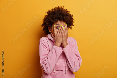 Photo Intrigued curious dark skinned woman peeks through fingers, covers face with pal