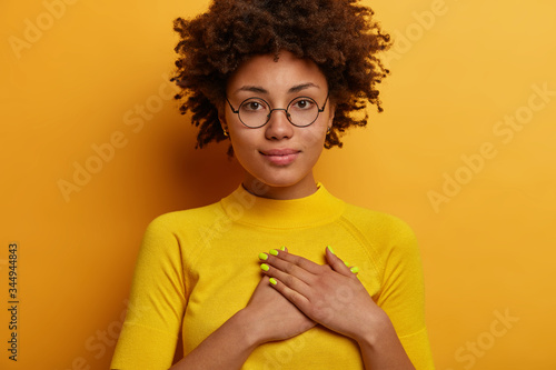 Serious calm Afro woman presses hands to heart in grateful gesture, appreciates nice words, expresses gratitude for received gift, wears yellow clothes in one color with wall, listens congratulations