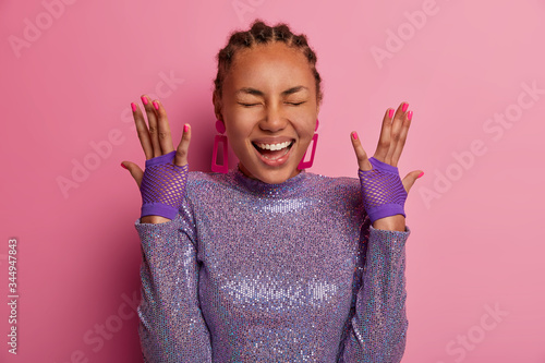 Photo Portrait of very happy amused woman has dark skin, raises hands, shows sport glo