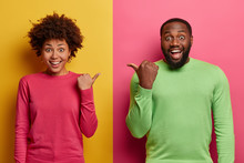 Positive Dark Skinned Woman And Man Point At Each Other With Thumbs, Wear Basic Clothes, Have Good Mood, Suggest Picking Friend, Isolated On Yellow And Pink Background. Look At My Companion.
