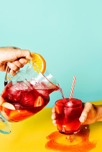 Man Pouring Sangria Punch In Glass