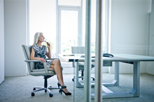 Thoughtful Businesswoman Sitting On Chair In Office