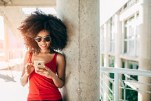 Young Afro Woman Texting Using...