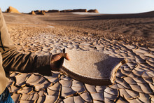 Male Hand Holding A Piece Of Dry Clay In The Desert