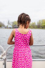 Child With Cornrow Braids And Pink Dress Looking Over The Side Of A Boat At Something Interesting In The Lake