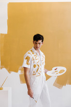 Young Man With Paint Palette Painting A Gold Background In White Coveralls
