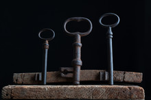 Three Old Rusty Keys Stand On Old Wooden Board Against A Dark Background