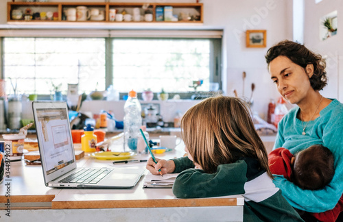 Mom accompanying her son in his homework while breastfeeding her baby Wallpaper Mural