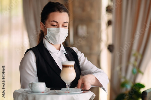 A female Waiter of European appearance in a medical mask serves Latte coffee Wallpaper Mural