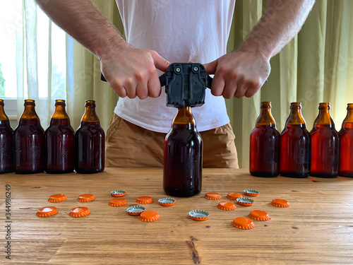 Cuadros en Lienzo Craft beer brewing at home, man closes brown glass beer bottles with plastic capper on wooden table with orange crown caps
