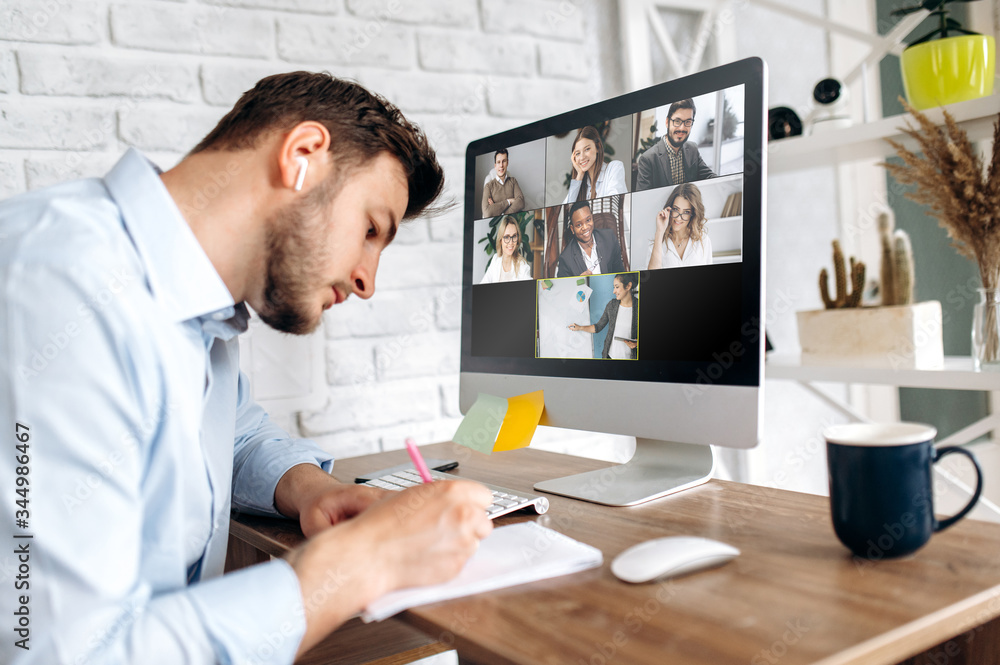 Fototapeta Online training. Young guy learns online by video conference in zoom app. On the screen, the teacher tells the information to him and other participants in the conference
