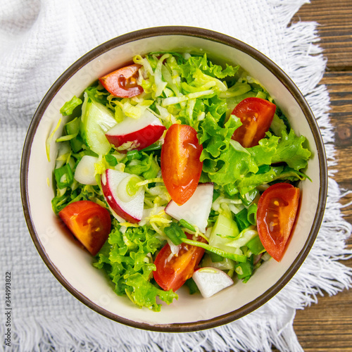 Fototapety, obrazy: The concept of healthy kitchen. Salad of fresh herbs, radish, cucumber and tomatoes with oil on a white napkin on rustic wooden background. Close-up, background image