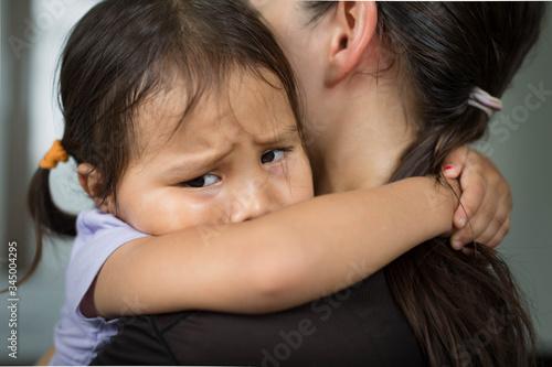 Canvas-taulu A sad child holding her mother for comfort and safety.