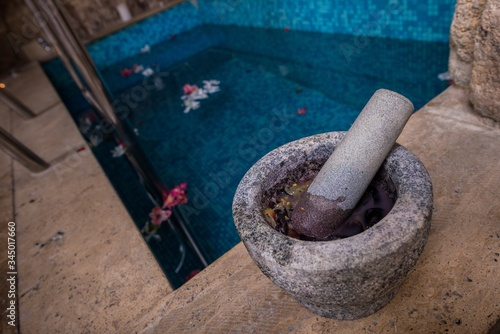 Closeup shot of mortar and pestle at the side of a pool Wallpaper Mural
