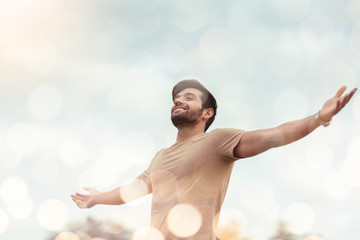 Happy Traveler male embracing life and enjoying freedom with open arms over sky and bokeh effect. Carefree smiling Bearded man standing relaxing and breathing fresh nature air at outdoor. Healthy life