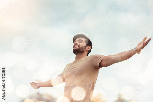 Fototapeta Happy Traveler male embracing life and enjoying freedom with open arms over sky and bokeh effect. Carefree smiling Bearded man standing relaxing and breathing fresh nature air at outdoor. Healthy life obraz